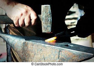 Blacksmith at work - Blacksmiths working process on metal at...