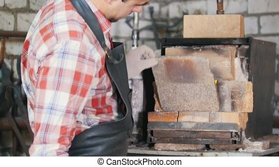 Blacksmith at work waiting for the worpieces in oven....