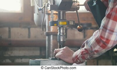 Blacksmith at work with electric drill machine, flying metal...