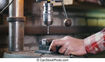 Blacksmith at work with electric drill machine, metal...
