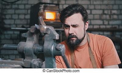 Blacksmith bends metal knife with gripe in workshop forge,...