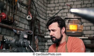 Blacksmith checks the symmetry of the knife blanks -...