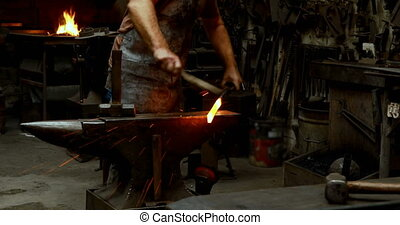 Blacksmith examining a hot metal rod with brush 4k -...