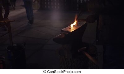 Blacksmith forges fierce metal hammer outdoors in evening. Hot iron. Sparks.