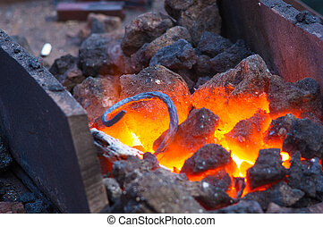 blacksmith furnace with burning coals, tools, and glowing...
