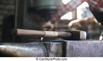 Blacksmith getting a red-hot top of the axe. Hammer in...