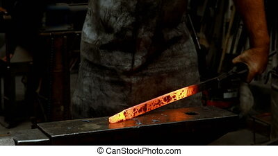 Blacksmith hammering a hot metal rod 4k - Blacksmith...