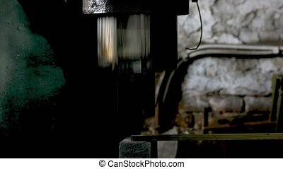 Blacksmith hammering iron with automatic hammer. Blacksmith ...