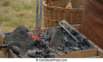 Blacksmith heating metal piece in outdoor forge at medival ...