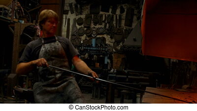 Blacksmith heating metal rod in fire 4k - Blacksmith heating...