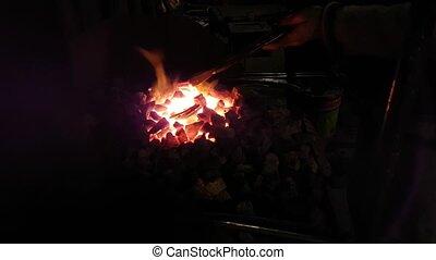 Blacksmith heats the horseshoe in the fire