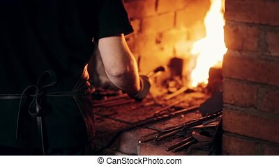 Blacksmith in apron at workplace. Close-up view of man gets out the hot metal from the furnace with fire.