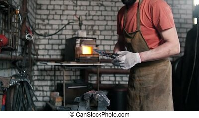 Blacksmith inspects the workpiece knife against the...