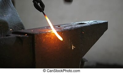 Blacksmith keeping a molten rod in tongues over a steel...