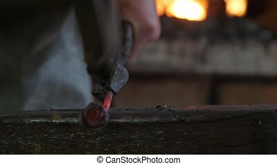 Blacksmith keeping and hitting a molten metallic rose in a...