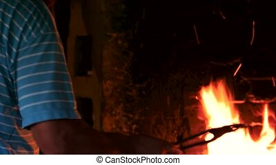 Blacksmith lightning fire in furnace. Blacksmith working at ...