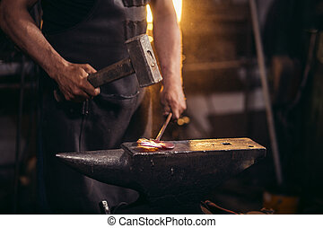 blacksmith manually forging molten metal on anvil in smithy...