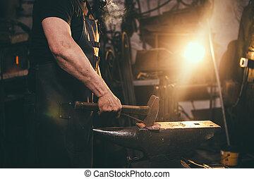 blacksmith manually forging molten metal on anvil in smithy...