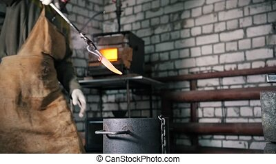 Blacksmith manually temper steel knife in engine oil,...
