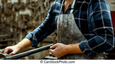 Blacksmith measuring metal rod with caliper 4k - Blacksmith...