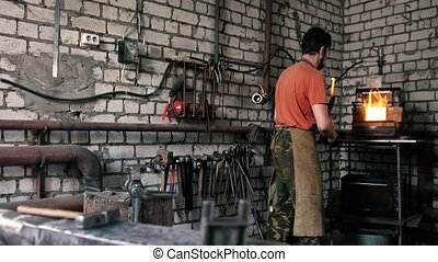 Blacksmith melts metal in the furnace - The blacksmith...