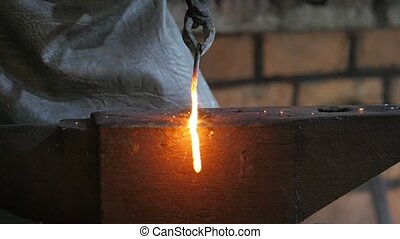 Blacksmith moving an iron rod in tongues over a steel anvil...