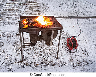 Blacksmith portable forge heating horse shoes for farm horses shoeing.