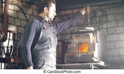 Blacksmith regulates the fire in the furnace with hot metal