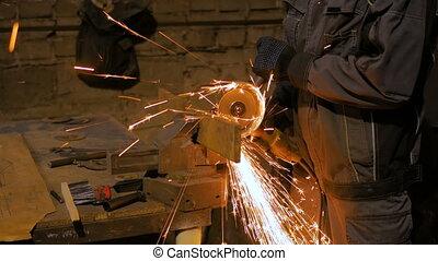 Blacksmith sawing metal with hand circular saw