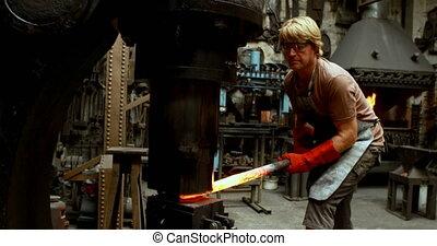 Blacksmith shaping hot metal rod in machine 4k - Blacksmith...