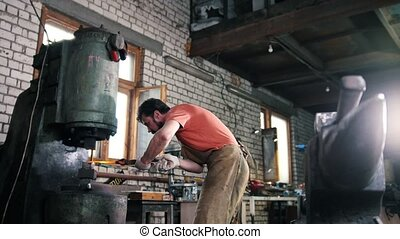 Blacksmith substitutes a metal piece for an automatic hammer...