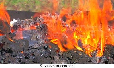 Blacksmith tongs glowing metal pat