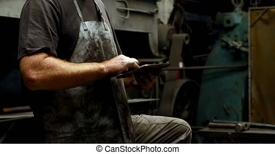Blacksmith using digital tablet in workshop 4k - Attentive...