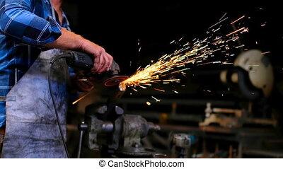 Blacksmith using grinder in workshop 4k - Side view of ...