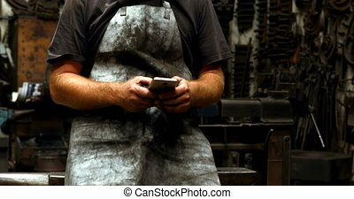 Blacksmith using mobile phone in workshop 4k - Attentive...