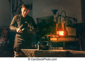 Blacksmith working in forge. - Blacksmith young man working ...