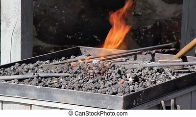 Blacksmith working on hot coal melting of an iron with fire