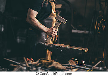 Blacksmith working on metal on anvil at forge high speed...