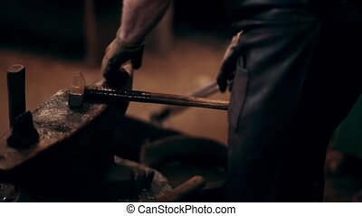 Blacksmith working on the anvil in smithy. Man puts the hot...