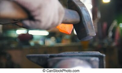 Blacksmith working with hammer. Close up red-hot detail -...