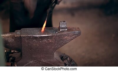 Blacksmith working with hammer on the anvil in the forge with hot metal. Close-up view of workplace.