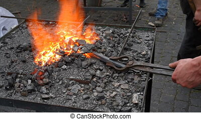 blacksmith working with molten iron at the festival of...