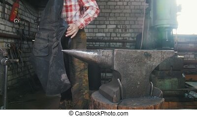 Blacksmith workroom. An anvil. Blacksmith is tying his work...