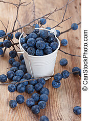 Blackthorn berry (sloe) on wooden table