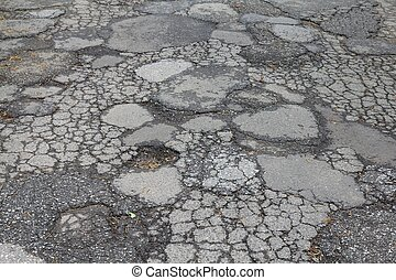 Road damage in Japan - cracked asphalt blacktop with potholes and patches