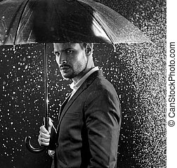Black&white portrait of a businessman posing in the middle of the storm