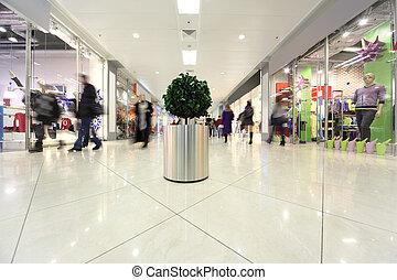 blanco, pasillo, en, centro comercial, árbol potted, y, gente en el movimiento