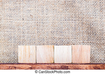 Blank 4 piece of cube wood on wood table and sack fabric...