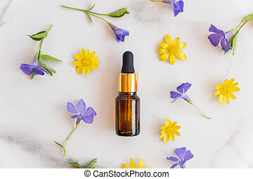 Blank amber glass essential oil bottle with pipette on marble background decorated blooming wild flowers. Skin care concept with natural cosmetics.