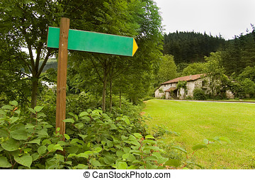 Blank arrow sing indicating to a antique house in a forest